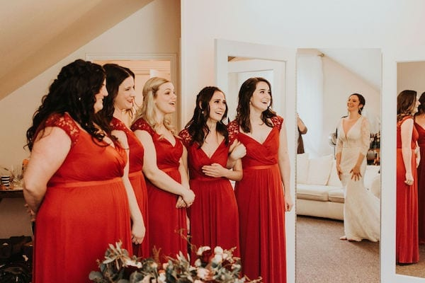 Mountain House Estate – Wine country winter wedding – Mountain House Estate wedding - bride revealing wedding gown- wedding party - bridesmaids in red dresses