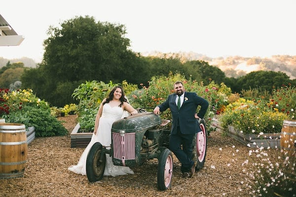 bride and groom with 1941 Ford tractor at Mountain House Estate garden and shed venue