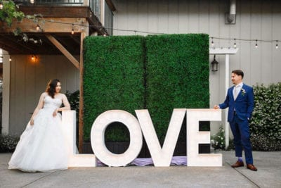 bride and groom next tot LOVE sign and boxwood wall